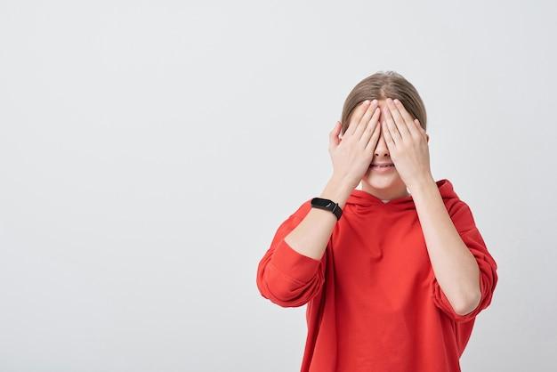 Smiling teenage girl in red hoodie couvrant ses yeux par les mains pendant le jeu de cache-cache en se tenant debout devant la caméra