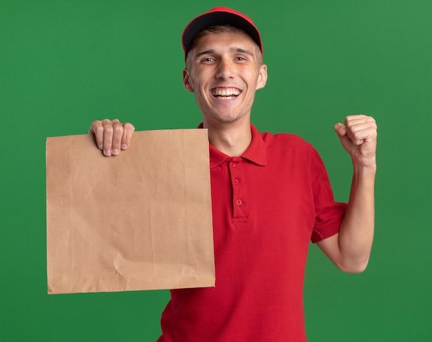 Smiling young blonde livreur garde le poing et détient le paquet de papier sur le vert