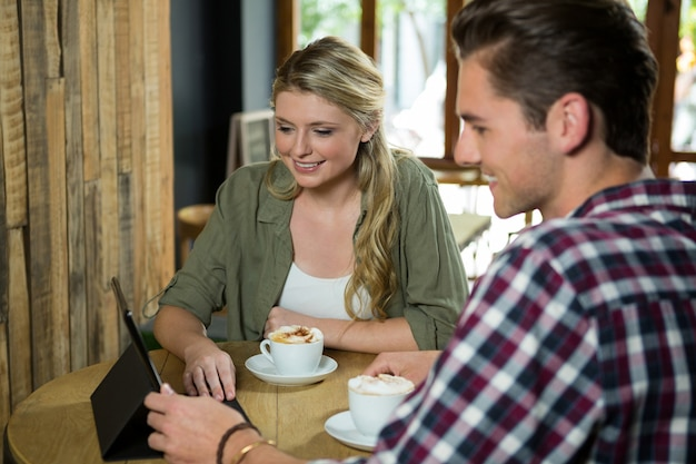 Smiling young couple using digital tablet at table in cafe