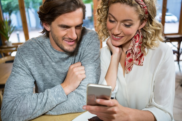 Smiling young couple using mobile phone at table in cafe