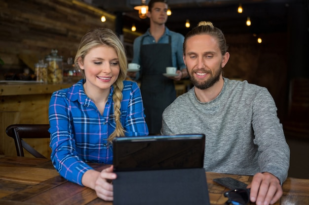 Smiling young couple using tablet computer at table in coffee shop