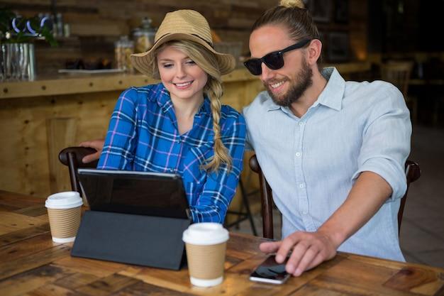 Smiling young couple using tablet pc à table en cafétéria