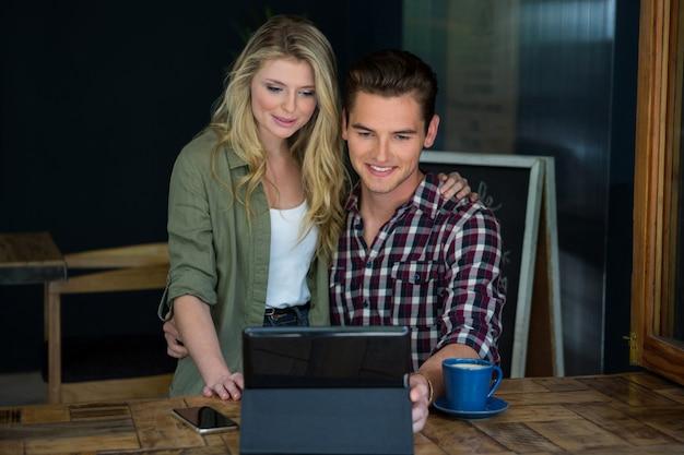 Smiling young couple using tablet pc à table dans un café
