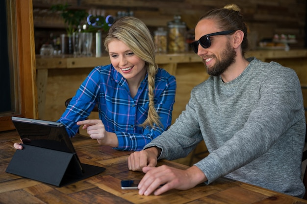 Smiling young couple using tablet pc à table in cafe