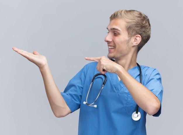 Smiling young male doctor wearing doctor uniform with stethoscope faisant semblant de tenir et pointe quelque chose d'isolé sur un mur blanc avec copie espace