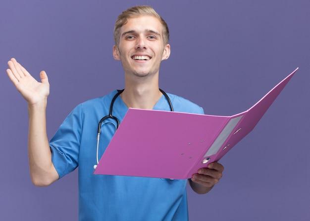 Smiling young male doctor wearing doctor uniform with stethoscope holding folder et diffusion de la main isolée sur le mur bleu