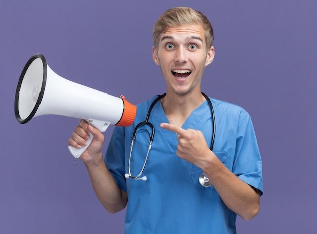 Smiling young male doctor wearing doctor uniform with stethoscope holding et points au haut-parleur isolé sur mur bleu