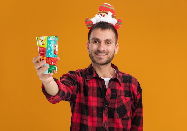 Smiling young man wearing santa claus headband étendant la tasse de noël en plastique vers la caméra en regardant la caméra isolée sur fond orange avec copie espace
