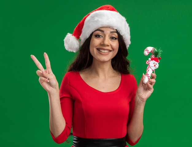 Smiling young pretty girl wearing santa hat holding candy cane ornement regardant la caméra faisant signe de paix isolé sur fond vert