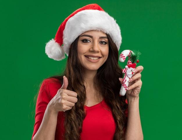 Smiling young pretty girl wearing santa hat holding candy cane ornement regardant la caméra montrant le pouce vers le haut isolé sur fond vert