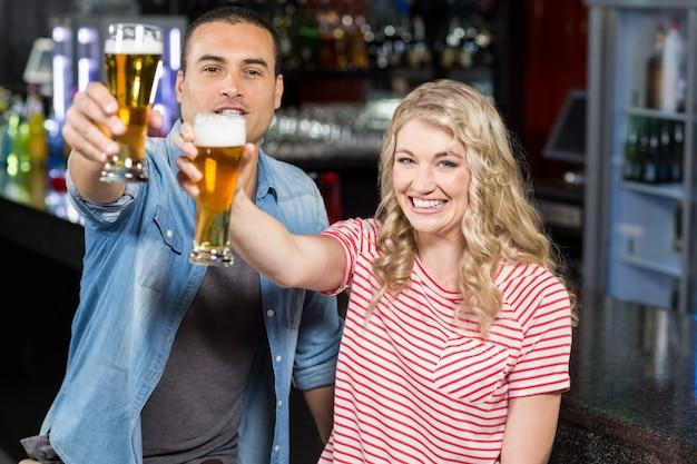 Smilinh couple holding bière
