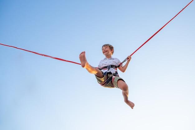 Smilling garçon excité sautant sur un trampoline avec assurance.