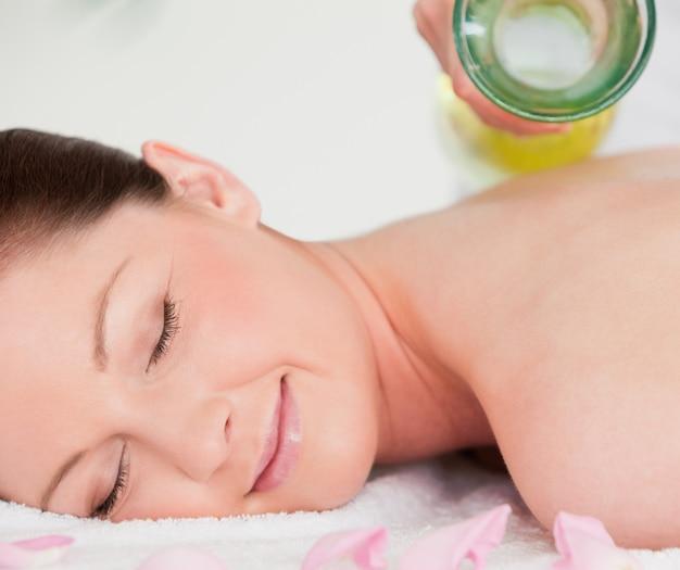 Smilling jeune femme ayant l'huile de masse versée sur son dos