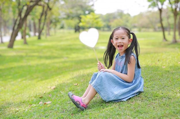Smilling petite fille asiatique tenant étiquette coeur blanc se trouvant sur l'herbe verte au jardin d'été.