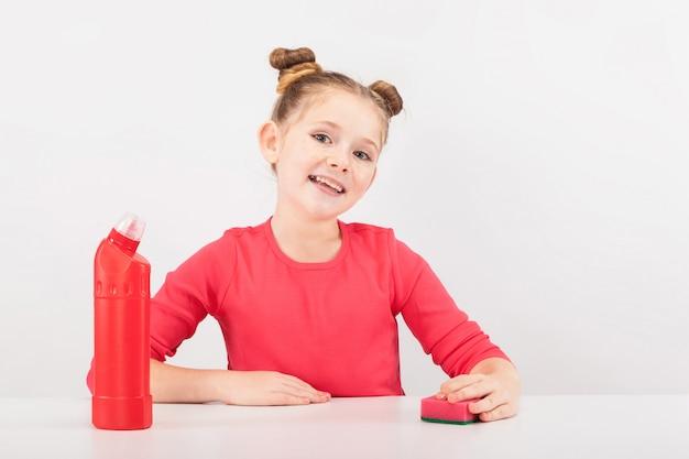 Smilng fille avec un nettoyant rouge et une éponge
