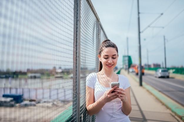 Smling fille se penchant sur une grille. écouter de la musique et utiliser un téléphone debout sur un trottoir.