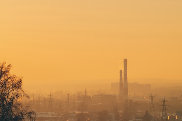 Smog parmi les silhouettes des bâtiments au lever du soleil.