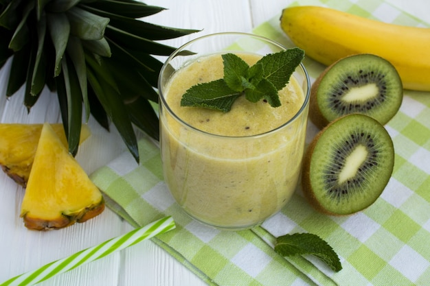 Smoothie à l'ananas, kiwi et banane sur la serviette verte