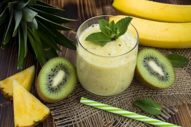 Smoothie à l'ananas, kiwi et banane sur la table en bois rustique