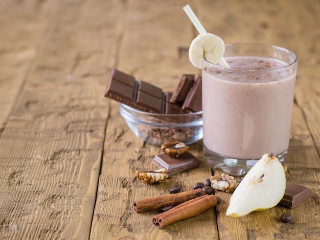 Smoothie au chocolat avec banane et poire sur table rustique vintage.