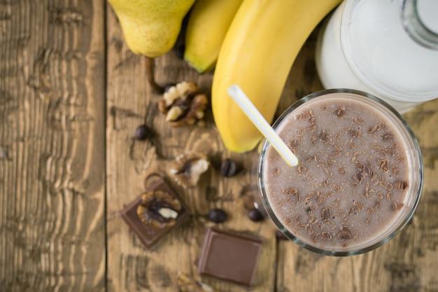 Smoothie au chocolat avec vue de dessus banane et noix.
