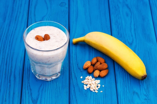 Smoothie au lait de banane et d'amandes dans un verre, mur bleu