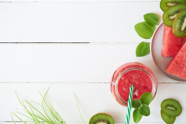 Smoothie au melon d'eau fraîche avec kiwi et menthe sur une table en bois blanche
