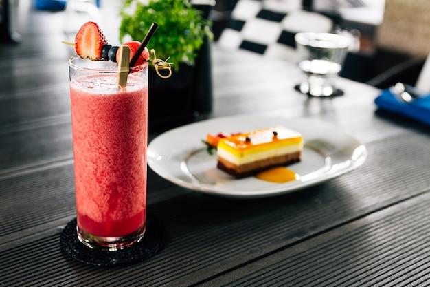 Smoothie aux baies mélangées servi avec des baies fraîches telles que la fraise, la mûre.