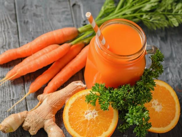 Smoothie aux carottes, deux moitiés d'orange, racine de gingembre et persil sur une table en bois.