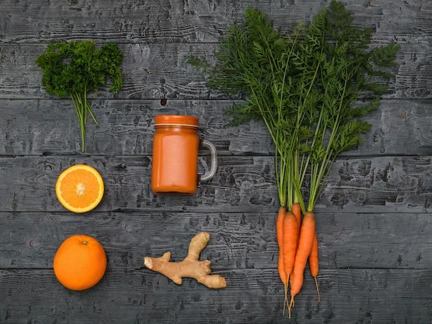 Smoothie aux carottes fraîchement préparé, bouquet de carottes, orange et racine de gingembre sur une table rustique