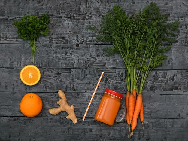 Smoothie aux carottes fraîchement préparé, bouquet de carottes, orange et racine de gingembre sur une table sombre et rustique.