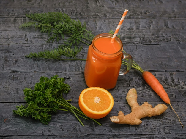 Smoothie aux carottes, moitiés d'orange, racine de gingembre et persil sur une table en bois.