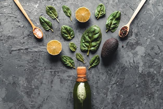 Smoothie aux épinards et au citron dans la bouteille. épinards frais dans des assiettes en bois. nourriture utile, écologique, végétalienne.