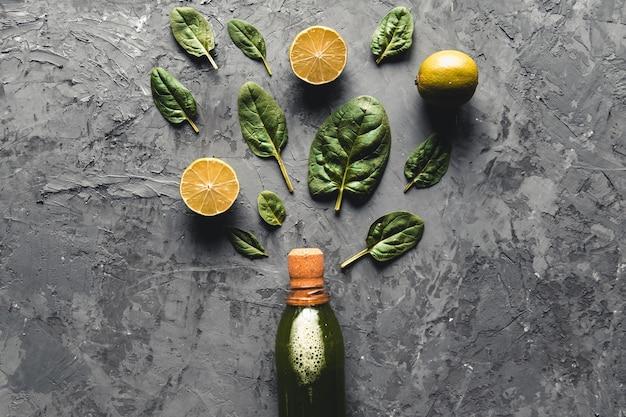 Smoothie aux épinards et au citron dans la bouteille. épinards frais dans des assiettes en bois.