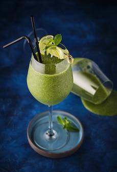 Smoothie aux épinards aux fraises au citron et à la menthe sur fond bleu. boire pour les végétaliens.