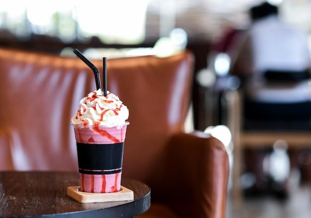 Smoothie aux fraises crème fouettée sur une table en bois.