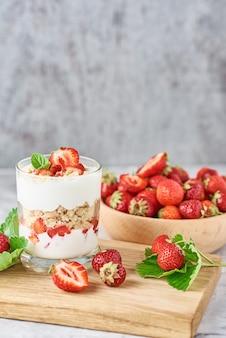 Smoothie aux fraises d'été dans un bocal en verre et des baies fraîches dans un bol en bois sur fond gris