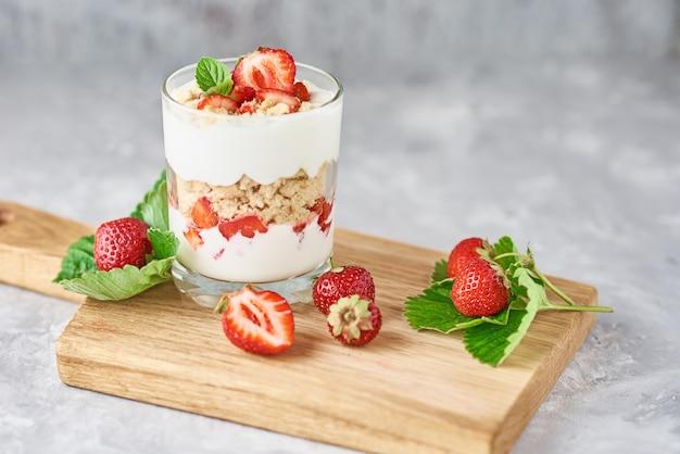 Smoothie aux fraises d'été dans un bocal en verre et des baies fraîches dans un bol en bois