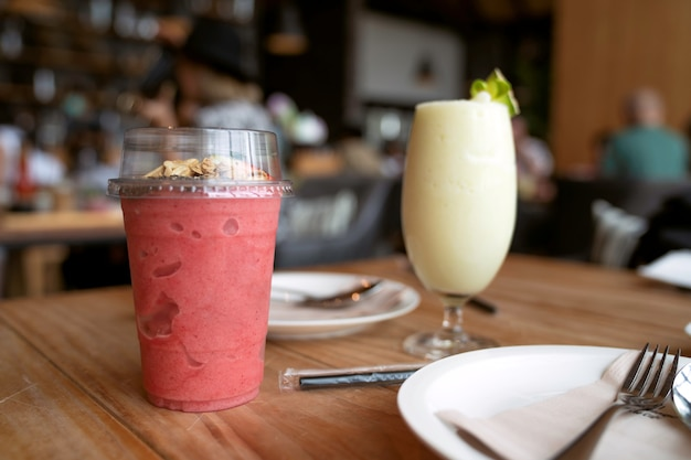 Smoothie aux fraises glacé en gros plan dans une tasse à emporter transparente sur une table en bois au restaurant
