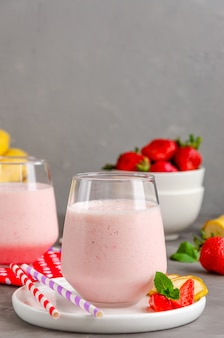 Smoothie aux fraises avec des pailles et des tranches de tranches de fruits frais