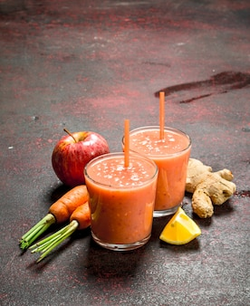 Smoothie aux fruits dans des verres sur table rustique.