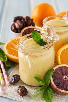 Smoothie aux fruits orange et dattes sains et frais sur une table en bois bleue. mise au point sélective.
