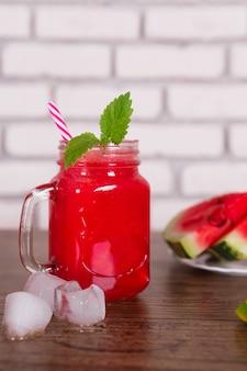 Smoothie aux fruits rouges mélangé dans un bocal en verre avec de la paille et des morceaux de glace. tranches de melon d'eau sur une assiette. mise au point sélective. récolte .