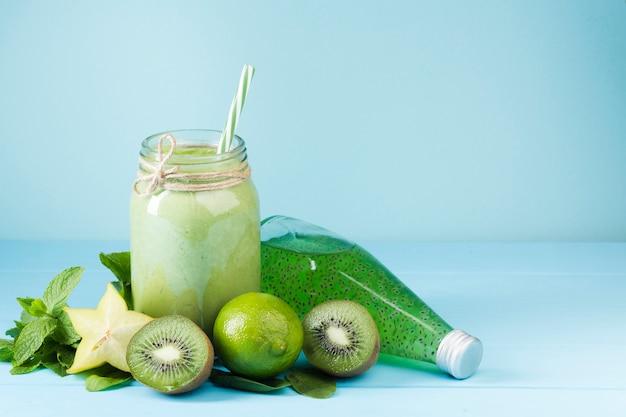 Smoothie aux fruits verts et jus sur fond bleu