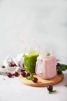 Smoothie aux herbes fraîches et smoothie aux cerises dans des bocaux en verre sur un support en bois