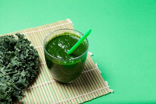 Smoothie aux légumes verts biologiques frais avec des feuilles de chou frisé sur fond vert