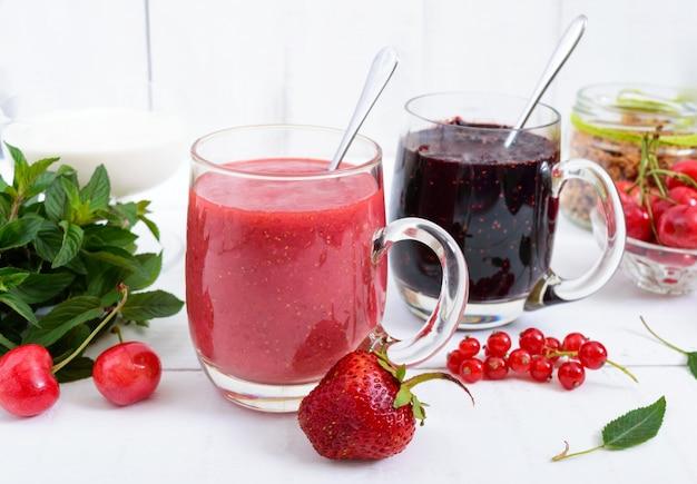 Smoothie aux petits fruits dans des tasses en verre, yaourt, granola, fruits frais sur fond de bois blanc. nutrition adéquat. petit-déjeuner sain. menu diététique.