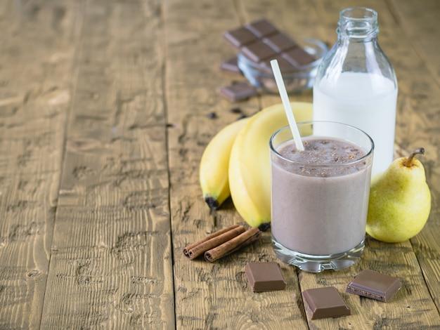 Smoothie banane au chocolat, poire et cannelle sur une table en bois.