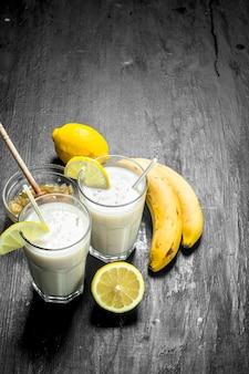 Smoothie à la banane, au citron et au lait. sur fond rustique.