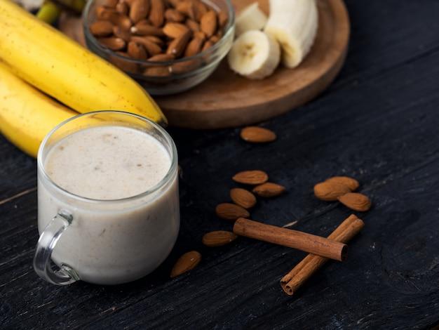 Smoothie banane fraîche aux amandes sur un fond en bois